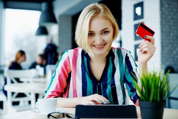 태블릿, 신용 카드와 커피 한잔, 프리랜서 개념, 온라인 쇼핑 카페에 앉아 화려한 셔츠를 입고 가벼운 머리를 가진 아름 다운 소녀.