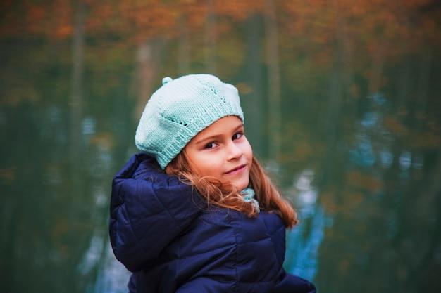 秋の公園で長いブロンドの髪を持つ美しい少女。黄色い紅葉を背景に金色の髪の毛を持つ茶色の目の少女