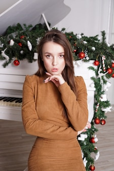 Beautiful girl with long blond hair near a white grand piano with christmas decor
