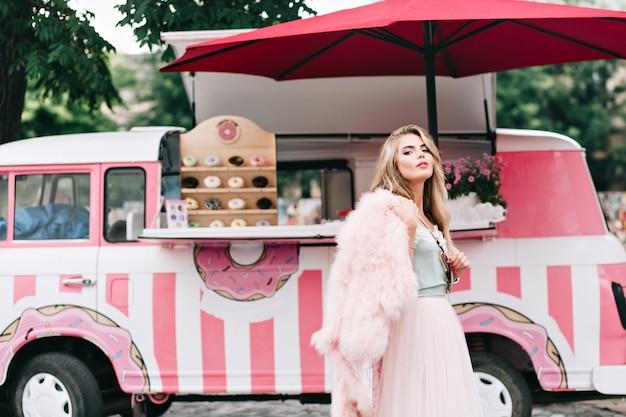レトロなコーヒー車の背景にチュールスカートで長いブロンドの髪を持つ美しい少女。カメラに見えます。