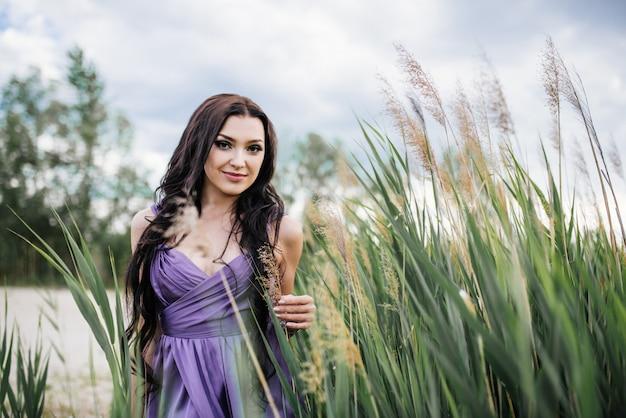 Красивая девушка с длинные каштановые волосы в фиолетовое платье в поле на закате. восточная внешность. восточный