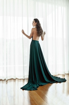 Beautiful girl with long curly hair posing in a beautiful evening dress with an open back.