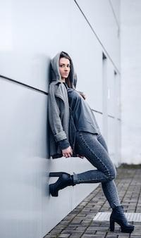 灰色のスウェットシャツと白い壁の背景にかかとで長い黒髪の美しい少女