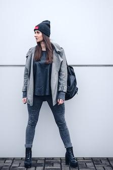 ベニー、かかとと白い壁の背景にバックパックと長い黒髪の美しい少女