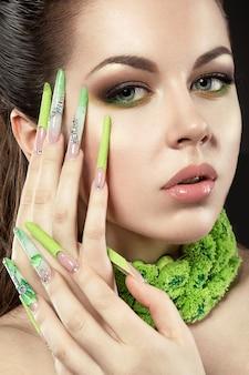 긴 녹색 손톱과 밝은 화장과 아름 다운 여자. 검정색 배경에 스튜디오에서 찍은 사진입니다.