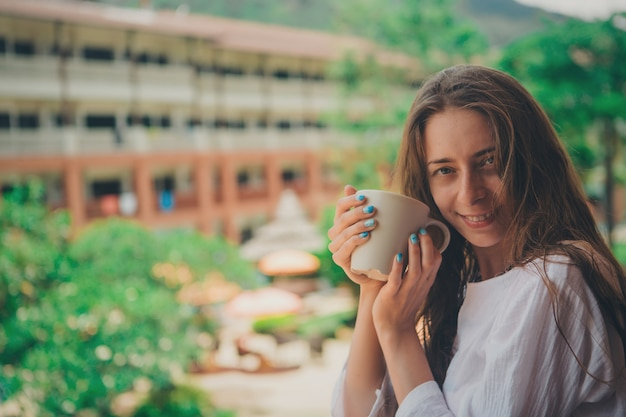 Beautiful girl with long hair and blue manicure holding a large mug