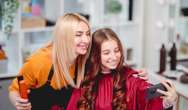 長い髪の美しい少女はサロンで美容師とselfieを作る髪型をカールします