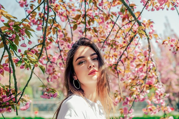 Beautiful girl with long hair enjoys the beauty of spring nature near the blossoming sakura tree.