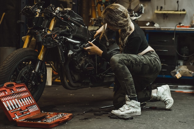 Beautiful girl with long hair in the garage repairing a motorcycle