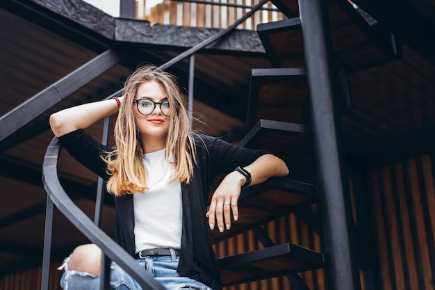 Beautiful girl with long hair and glasses sitting on metal stairs