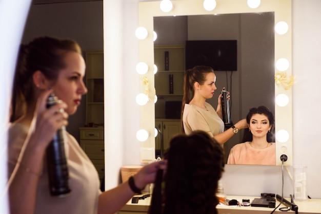 긴 머리를 가진 아름 다운 소녀, 미용사는 미용실에서 프랑스 머리를 엮어 냈다. 전문 헤어 케어 및 헤어 스타일 만들기