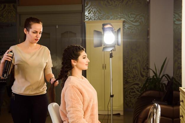 長い髪の美しい少女、美容師は美容院で、フランスの三つ編みを織ります。プロのヘアケアとヘアスタイルの作成。