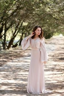 Красивая девушка с длинными волосами в легком платье стоит в лесу