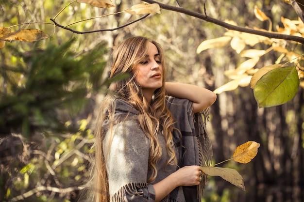 Красивая девушка с длинными волосами в осеннем лесу, концепция осеннего сезона