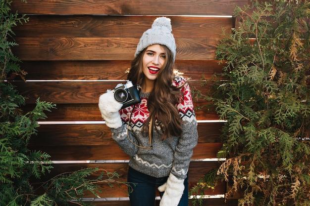 Bella ragazza con capelli lunghi in cappello lavorato a maglia e guanti bianchi su rami verdi circondano in legno. indossa un maglione caldo, tiene la macchina fotografica, sembra goduta.