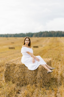 Beautiful girl with long hair in a long white dress sitting on a haystack in a field