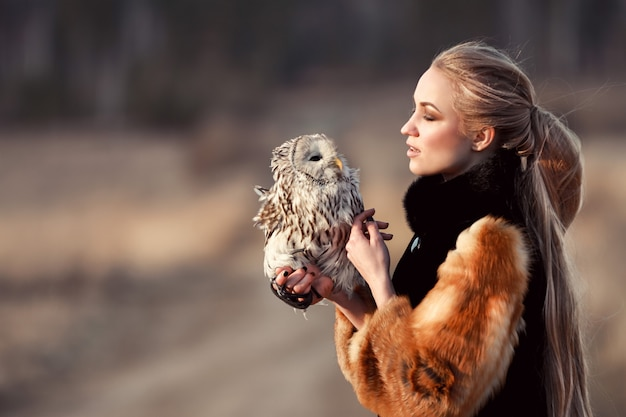 Beautiful girl with long hair nature, holding owl