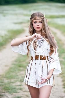 自然でポーズをとって長い髪の美しい少女