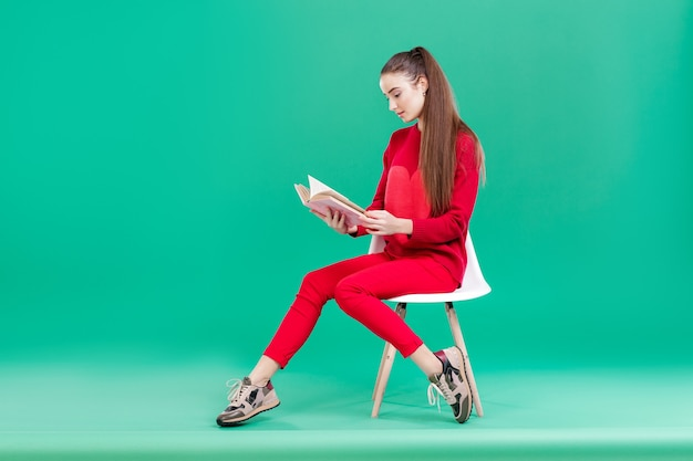 Beautiful girl with long hair in red sweater reads book. copy space