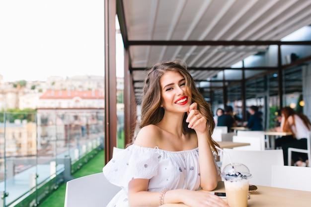 Красивая девушка с длинными волосами сидит за столом на террасе в кафе. она носит белое платье с открытыми плечами и красной помадой. она улыбается в камеру.