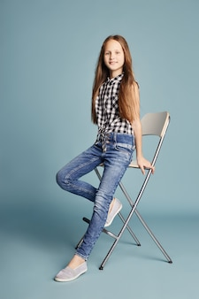 Beautiful girl with long hair sitting on chair