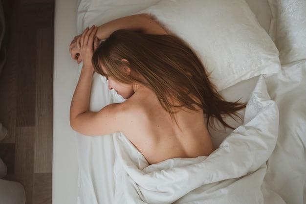 長い髪の美しい少女は白いシーツで彼女のベッドで眠る