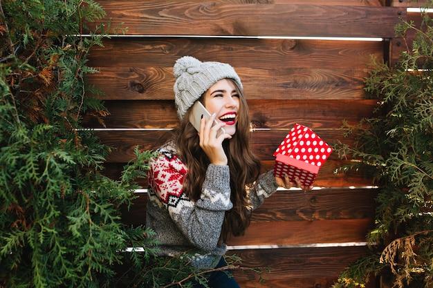 Bella ragazza con i capelli lunghi con scatola di natale sui rami verdi circondano in legno. indossa abiti invernali caldi, parla al telefono, ride di lato.