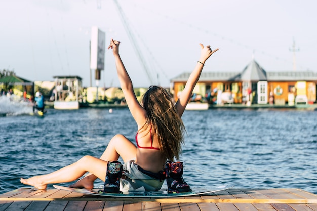 Beautiful girl with long hair with a wakeboard