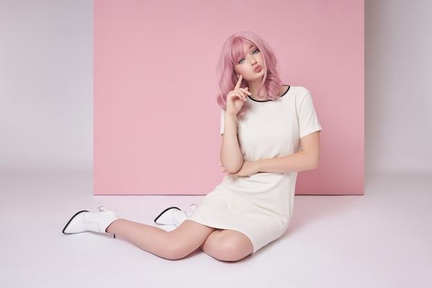 Красивая девушка с длинными розовыми волосами, сидя на полу, окраска волос. милая женщина на розовом фоне в коротком белом платье. цветные волосы, идеальная прическа