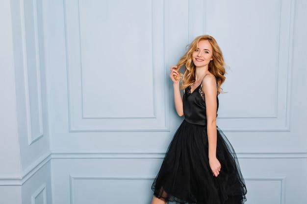 Красивая девушка с длинными волнистыми светлыми волосами позирует в комнате с синей стеной, веселая элегантная юная леди в черном кружевном платье. она улыбается и трогает свои волосы.