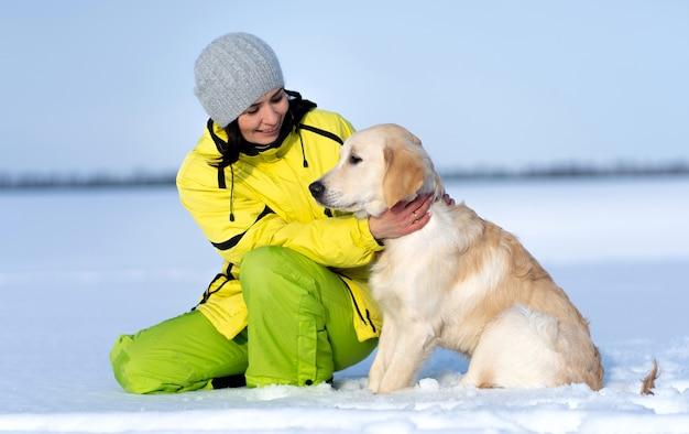 Красивая девушка с милой молодой собакой ретривера на улице зимой