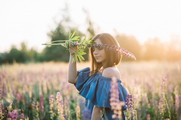 Beautiful girl with a lupine flower in her hands in a field at sunset. soft focus.