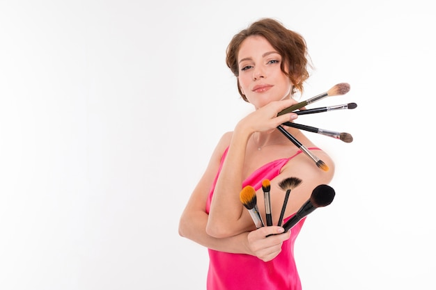 Beautiful girl with makeup brushes on a white wall with copywriting