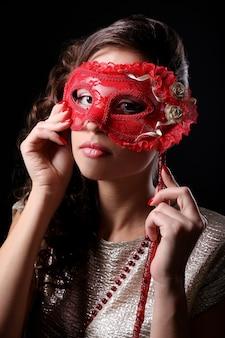 Красивая девушка с маскарадной маской на темноте