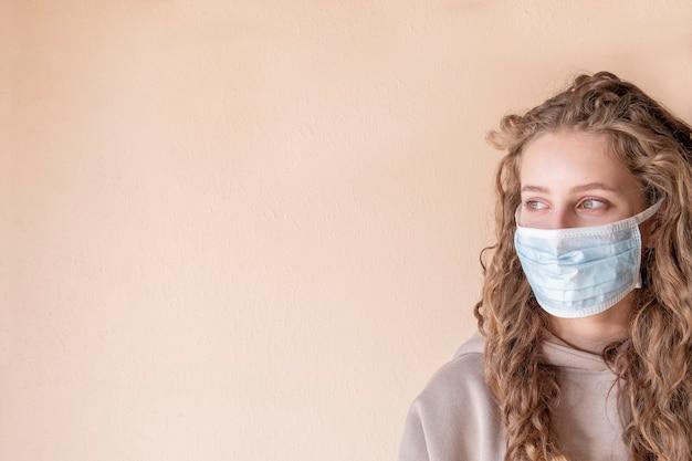 医療用防護マスクを持つ美しい少女。テキストスペース