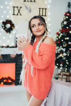 Beautiful girl with naked sexy legs in a sweater holding a gift box near her ear