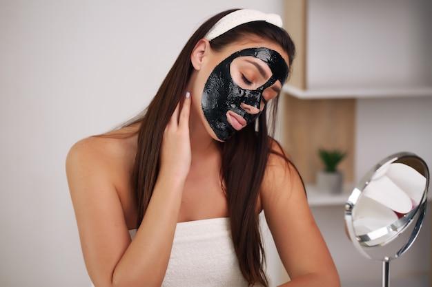 Красивая девушка с естественным макияжем дома концепция красоты и ухода за кожей