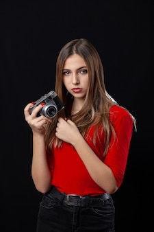 Beautiful girl with oldstyle camera posing in red shirt on black background. teenager.