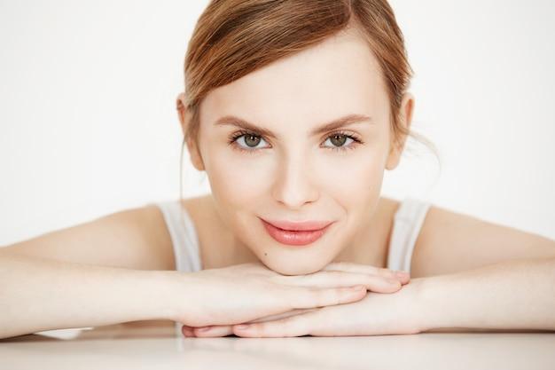 Красивая девушка с идеально чистой кожей, улыбаясь, сидя за столом. салон красоты и спа.