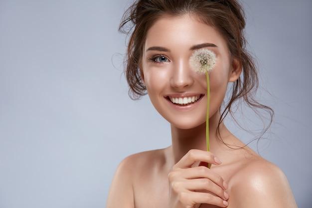 Красивая девушка с идеальной улыбкой, закрывая один глаз цветком одуванчика на сером фоне