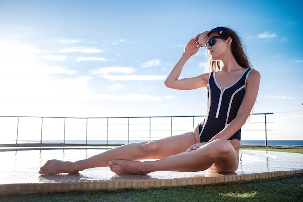 Beautiful girl with perfect tanned body in in blue one piece bathing suit