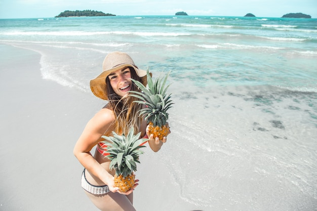 Beautiful girl with pineapple on an exotic beach, a happy mood and a beautiful smile, top view