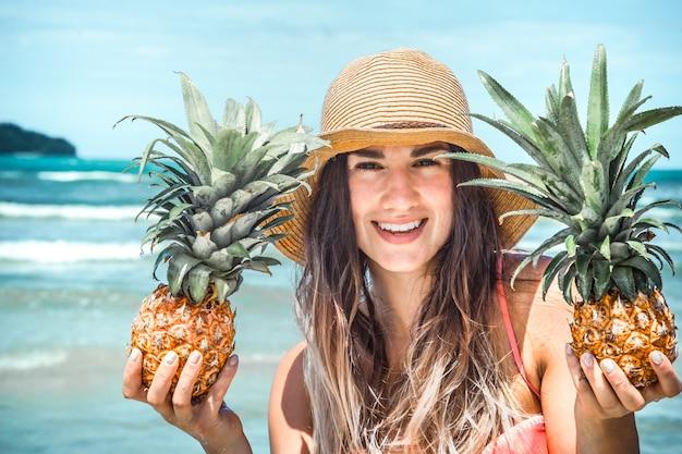 Bella ragazza con ananas su una spiaggia esotica, uno stato d'animo felice e un bel sorriso