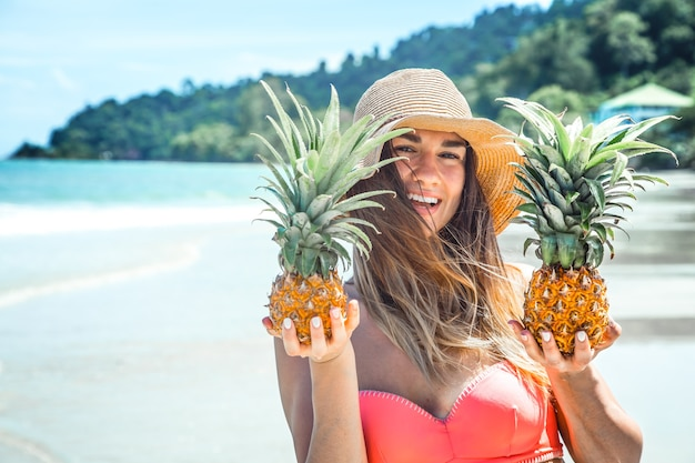 Красивая девушка с ананасом на экзотическом пляже, счастливое настроение и красивая улыбка, крупным планом