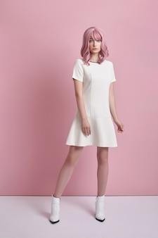 ピンクの髪、髪の色を持つ美しい少女。かわいいアニメの女性は短い白いドレスを着てピンクの背景に立っています