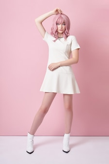 Beautiful girl with pink hair, hair coloring. cute anime woman stands on a pink background in a short white dress. colored hair, perfect hairstyle