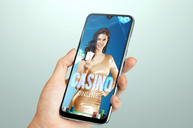 스마트 폰 화면에 그녀의 손에있는 카드 놀이와 아름 다운 소녀. 온라인 카지노, 도박, 도박, 룰렛. 전단지, 포스터, 광고 템플릿. 복사 공간.