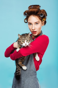 Beautiful girl with pretty cat in hands posing and looking