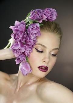 Красивая девушка с фиолетовыми тюльпанами цветки. лицо женщины модели красоты. идеальная кожа. профессиональный макияж. искусство моды