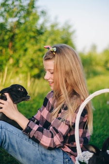 Beautiful girl with a rabbit. girl laughs and kisses a rabbit. card shirt and jeans. easter bunny. laugh out loud